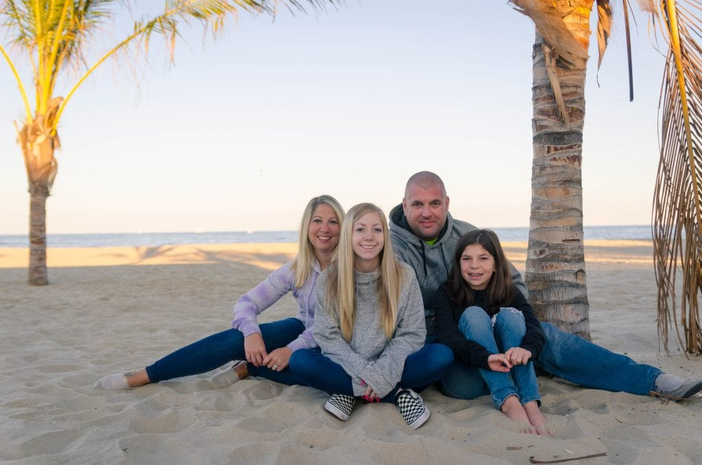 family on Point Pleasant, NJ beach under a palm tree in jeans and hooded sweatshirts or hoodies for a family portrait by LaGregor Photography