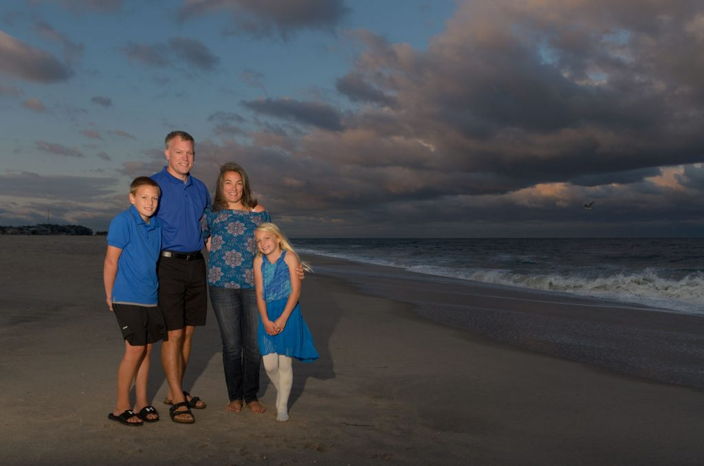 Family wearing various variations of blue clothes on Point Pleasant Beach, NJ with a dramatic sunset sky for a family portrait by LaGregor Photography